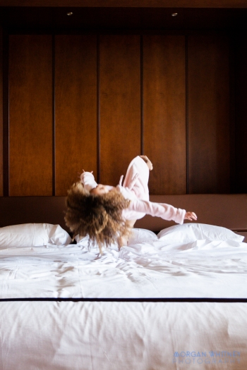 little girl jumping on the bed